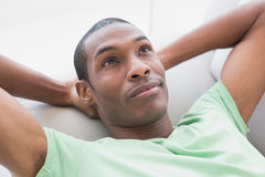 Thoughtful relaxed young Afro man lying on sofa Stock Images