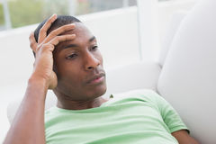 Thoughtful relaxed young Afro man lying on sofa Royalty Free Stock Photos