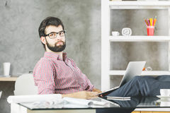 Thoughtful relaxing man with laptop. Thoughtful relaxing caucasian businessman in modern designer office using laptop. Success concept Stock Image