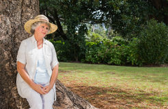 Thoughtful retired woman sitting on tree trunk Royalty Free Stock Photo