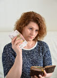 Thoughtful Russian woman pulls from her purse rubles Royalty Free Stock Photo