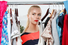 Thoughtful sad blonde woman stand near wardrobe rack Stock Images