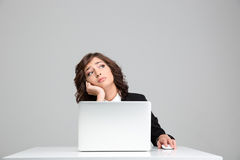 Thoughtful sad business woman dreaming sitting at the laptop Stock Images