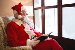 Santa claus reading novel in living room during christmas time Royalty Free Stock Photography