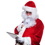 Thoughtful santa claus reading wishes on tablet pad Royalty Free Stock Photos