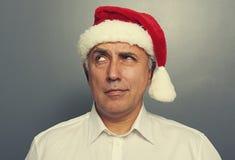 Thoughtful santa man over dark Stock Images