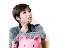 Thoughtful about savings and piggy bank Royalty Free Stock Photo