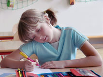Thoughtful school girl. School girl writing an assignment in classroom stock photos