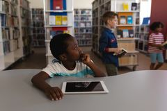 Thoughtful schoolboy with hand on chin looking away sitting at table in school library. Front view of thoughtful schoolboy with hand on chin looking away sitting stock image