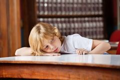 Thoughtful Schoolboy Leaning On Table In Library. Thoughtful little schoolboy looking away while leaning on table in library Royalty Free Stock Photography