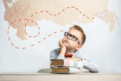 A thoughtful schoolboy sits at a desk with books. Above him flies an imaginary airplane made of paper royalty free stock image