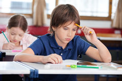 Thoughtful Schoolboy Sitting At Desk. With girl studying in background Stock Image