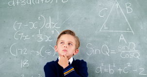 Thoughtful schoolboy standing in front of chalkboard stock video