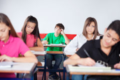 Thoughtful Schoolboy Studying In Classroom Stock Photography