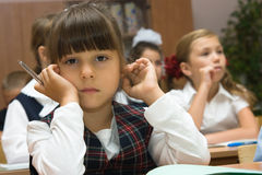 The thoughtful schoolgirl. Children at school at a lesson. The thoughtful girl sits at a school desk Royalty Free Stock Images