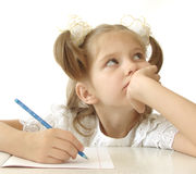 Thoughtful schoolgirl. Little pretty schoolgirl with pen and notebook Royalty Free Stock Photos
