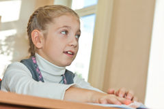 Thoughtful schoolgirl in classroom Stock Photo