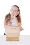 Thoughtful schoolgirl with pile of books Royalty Free Stock Images
