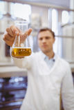 Thoughtful scientist holding a beaker Royalty Free Stock Images