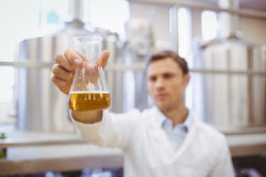 Thoughtful scientist holding a beaker Royalty Free Stock Image