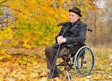 Thoughtful senior amputee sitting outdoors. In his wheelchair crutches hand enjoying last warmth autumn sun against  backdrop colourful yellow leaves Royalty Free Stock Photography