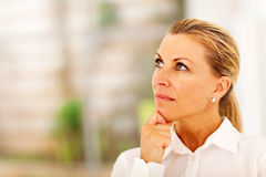 Thoughtful senior businesswoman. Looking up royalty free stock image
