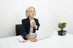 Thoughtful senior businesswoman having coffee at desk in office Stock Image