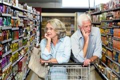 Thoughtful senior couple with cart Stock Photo