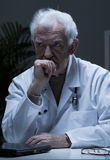 Thoughtful senior doctor Stock Photography