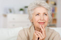 Thoughtful senior lady. Sitting at home with her fingers to her chin reminiscing and recalling fond memories, close up portrait Royalty Free Stock Image