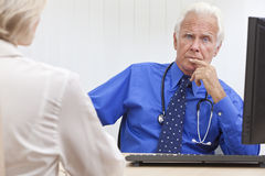 Thoughtful Senior Male Doctor With Computer. A senior male medical doctor looking thoughtful with a female patient and computer at his desk in an office at a stock image