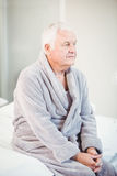 Thoughtful senior man in bathrobe sitting on bed Royalty Free Stock Images