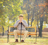 Thoughtful senior man with a cane sitting on bench in a park Royalty Free Stock Photos