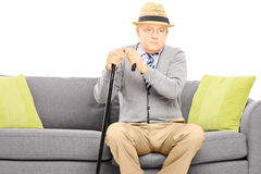 Thoughtful senior man with a cane sitting on a couch Stock Photo