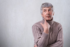 Thoughtful senior man dreaming about something looking up holding his hand under chin  standing against blank white wall with copy Royalty Free Stock Images