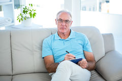 Thoughtful senior man in eyeglasses sitting on sofa with clipboard Royalty Free Stock Photography