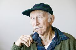Thoughtful Senior Man in a Hat and Glasses Stock Photography