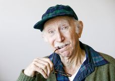 Thoughtful Senior Man in a Hat and Glasses Royalty Free Stock Image