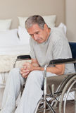 Thoughtful senior man in his wheelchair Royalty Free Stock Images