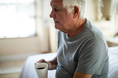 Thoughtful senior man holding mug of black coffee in the bedroom. At home Royalty Free Stock Photos