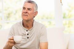 Thoughtful senior man holding mug. On the sofa Stock Images