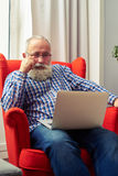 Thoughtful senior man with laptop. Thoughtful senior man sitting on the chair and looking at laptop at home royalty free stock photos