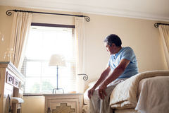 Thoughtful senior man looking through window in bedroom Royalty Free Stock Photos