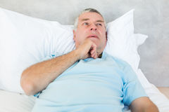 Thoughtful senior man lying in bed Stock Photos