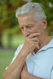 Thoughtful senior man  in  park Royalty Free Stock Image