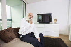 Thoughtful senior man sitting on sofa in living room Royalty Free Stock Photos