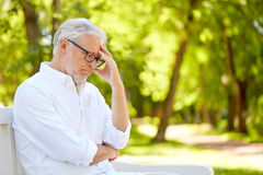 Thoughtful senior man sitting at summer park Royalty Free Stock Images