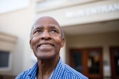 Thoughtful senior man smiling while looking up at nursing home. Close-up of thoughtful senior man smiling while looking up at nursing home Stock Image