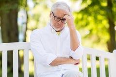 Thoughtful senior man at summer park Stock Photography