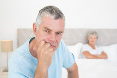 Thoughtful senior man with woman in background Royalty Free Stock Photos